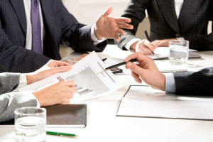 Close-up of business people hands with pens during explanation at meeting