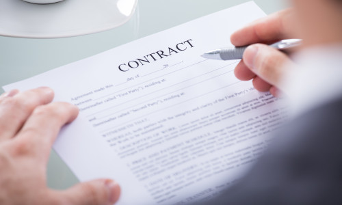 Close Up Of Businessperson Holding Pen On A Contract Paper