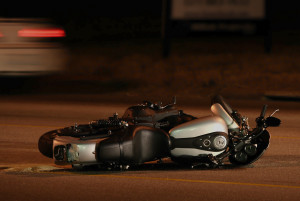 motorcycle lying on side in street with car speeding by in the background.
